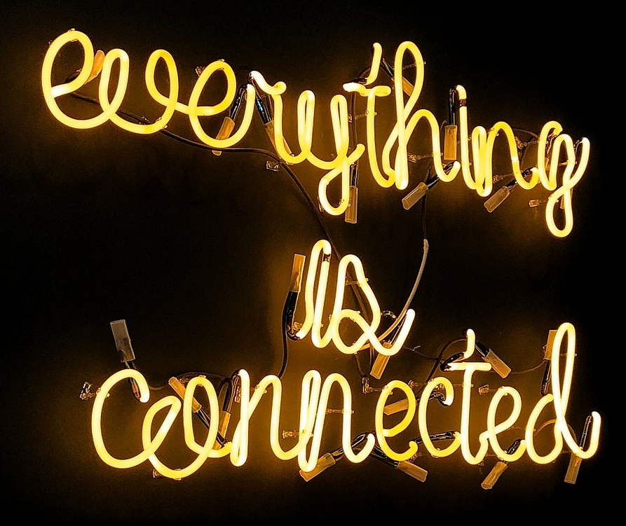 everything is connected, phrase in yellow neon tube