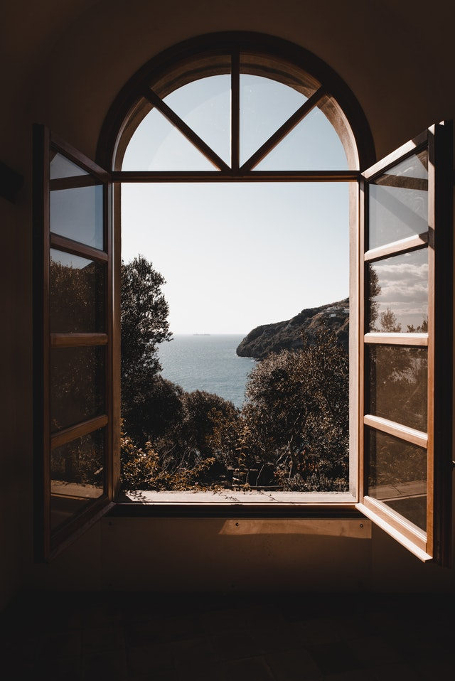 window opened inwards looking out onto sea