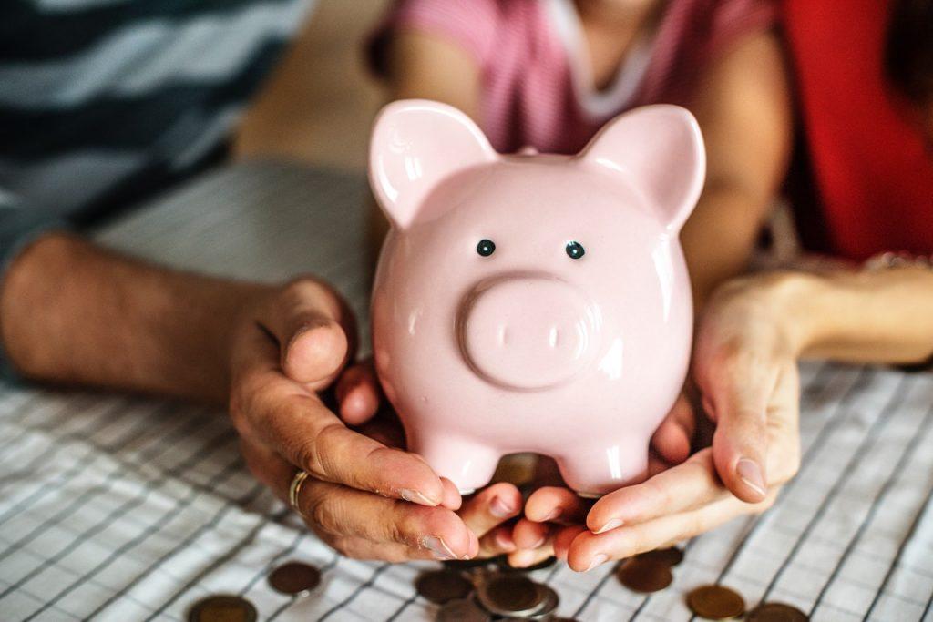 piggy bank in people's hands with coins below